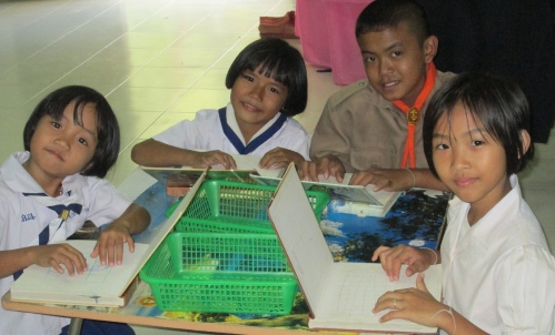 These third grader are 'playing computer' with books open  - just like a 'notebook'  which Thais in my village use to mean 'computer'.